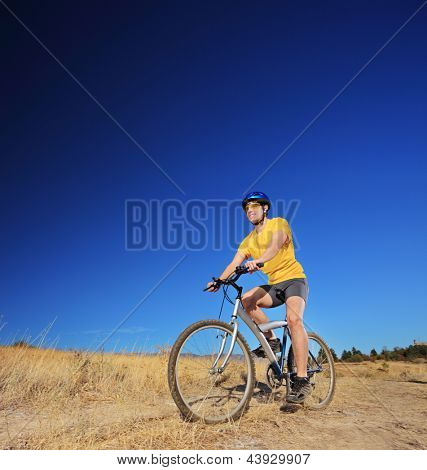 A young male with yellow shirt and helmet riding a mountain bike outdoors, shot with a tilt and shift lens