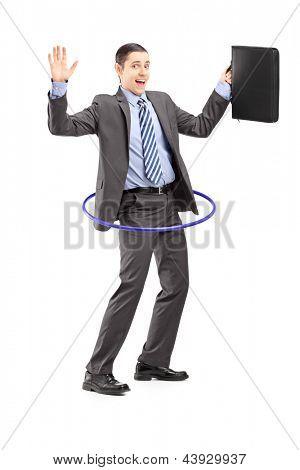 Retrato de corpo inteiro de um jovem empresário de terno segurando uma maleta e dançando com um bambolê