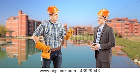 Male manual worker having a conversation with architect, buildings in the background