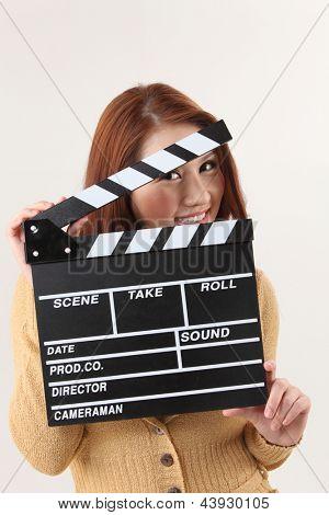 woman hiding behind the film slate