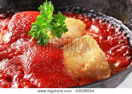 codfish fillet with tomato sauce in a iron pan