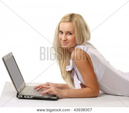 Portrait of a happy young business woman lying on the floor and working on a laptop. Isolated on white background