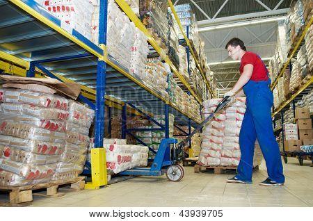 trabalhador com empilhador de caminhão de pálete de garfo no grupo de pacotes de comida de carregamento do armazém