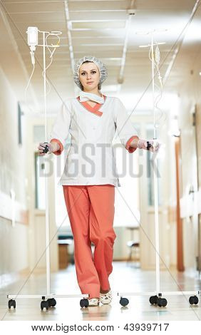 Young nurse doctor in medic uniform with droppers in hospital clinic hall