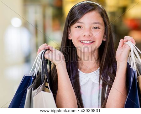 Happy girl on a shopping spree holding bags and smiling