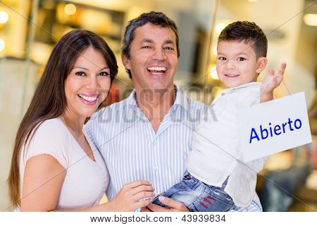 Family at the mall holding a Spanish open sign