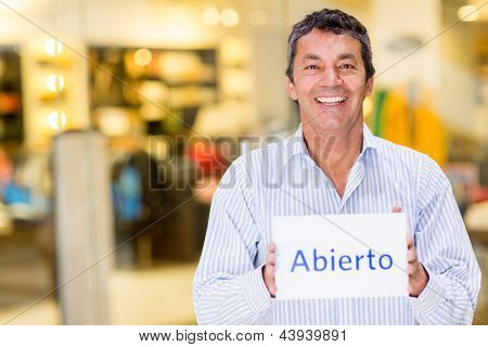 Happy man at a retail store with an open sign smiling