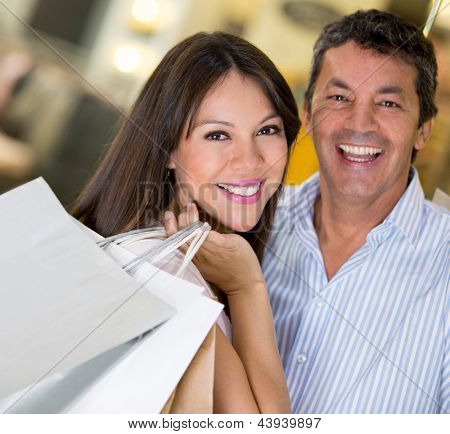 Happy couple shopping holding bags and smiling
