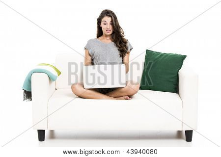 Beautiful woman on a sofa astonished with something in the laptop, isolated in white