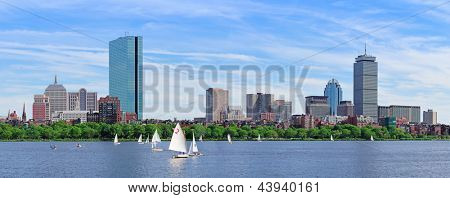Boston Charles River panorama with urban city skyline skyscrapers and boats with blue sky.