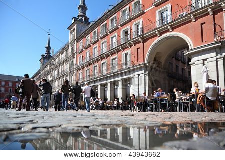 MADRID - MARCH 9: Tourists walk and sit at tables in cafe at Plaza Mayor on March 9 2012 in Madrid, Spain. In 2012 number of tourists in resorts of Spain increased 1.5 times compared to 2011.