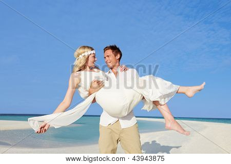 Groom Carrying Bride At Beautiful Beach Wedding