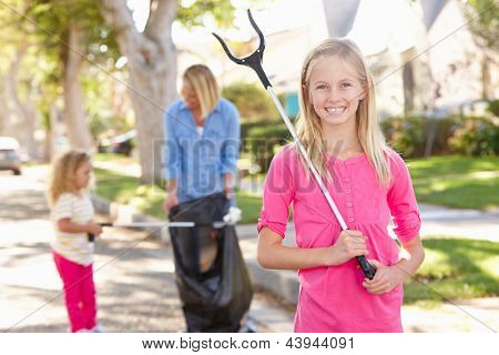 Madre e hijas levantando basura en la calle suburbana