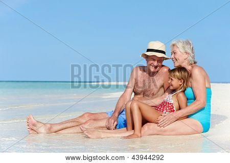 Grandparents With Granddaughter Enjoying Beach