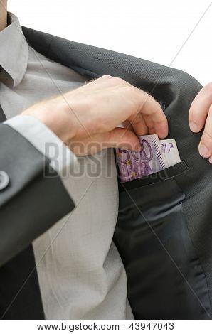 Man Putting Money In His Pocket