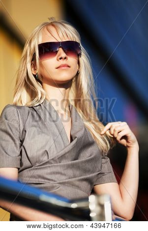 Beautiful blond woman against office windows