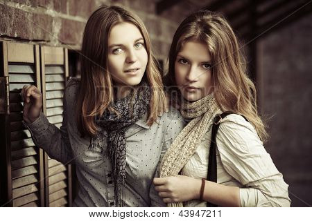 Young girls against a brick wall