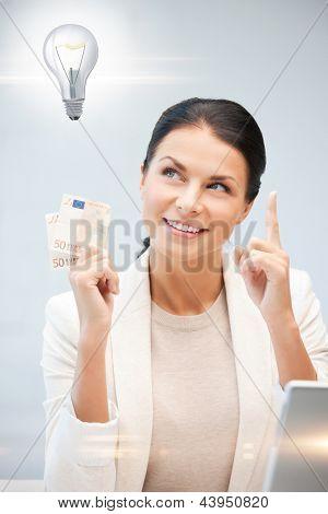 mujer feliz con dinero en efectivo euro y bombilla