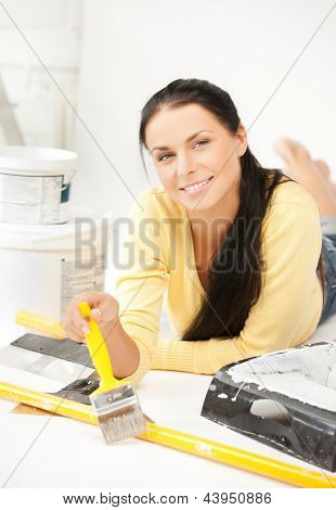 happy young woman with paintbrush and renovating tools