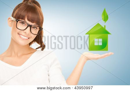 beautiful woman holding green house in her hands