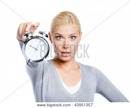 Woman in grey pullover showing the alarm clock, isolated on white