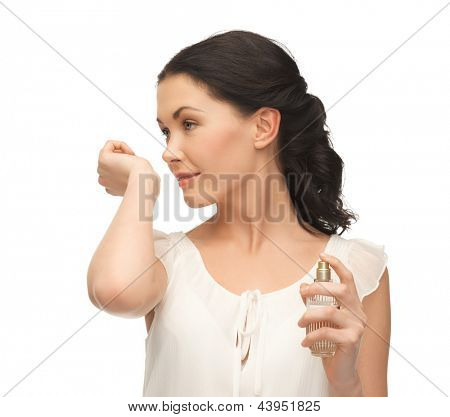 picture of beautiful woman smelling perfume on her hand