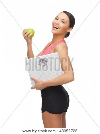 picture of beautiful sporty woman with scale and green apple
