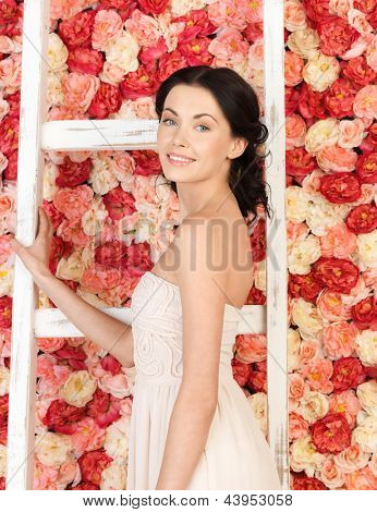 young woman with old ladder and background full of roses