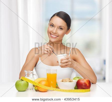 Junge Frau mit dem gesunden Frühstück und Maßband