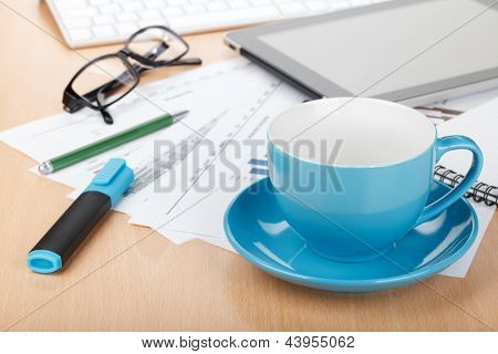 Coffee cup on contemporary workplace with financial papers, computer and office supplies