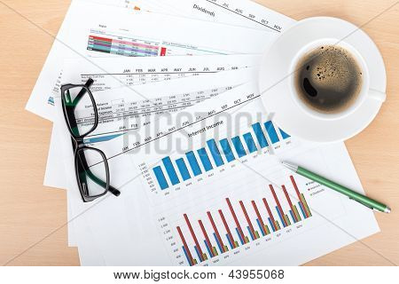 Coffee cup on contemporary workplace with financial papers, glasses and pen