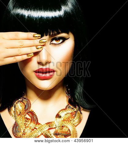 Golden Jewellery. Gold Jewelry. Beauty Brunette Egyptian Style Woman with Gold Accessories and Nails. Golden Nail Polish and Necklace