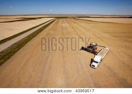 Aerial shot of a combine emptier a hopper into a semi truck on the prairie