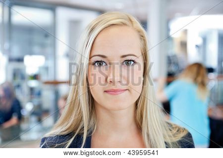 Close up portrait of a blonde young female owner of beauty parlor smiling