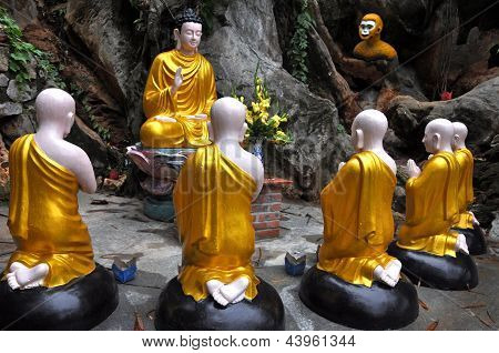 Gold sitting Buddha surrounded by monk students statues, Vietnam