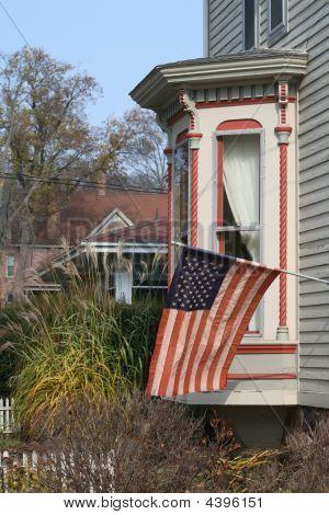 Antiga bandeira americana em uma casa vitoriana em uma cidade pequena