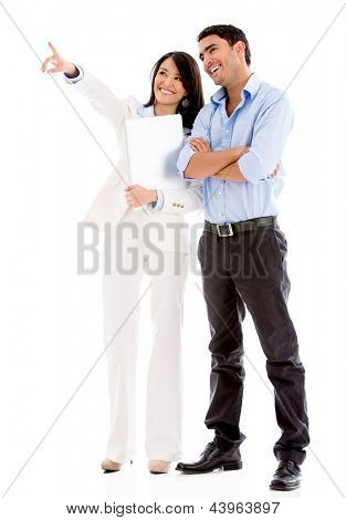 Successful business couple pointing away - isolated over white