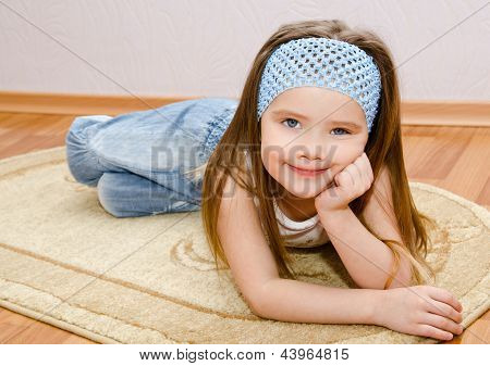 Smiling Little Girl Lies On A House Floor