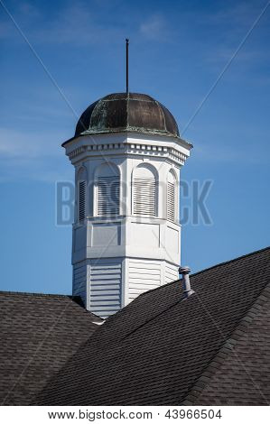 Old Tarnished Cupola On Roof Under Blue Skies