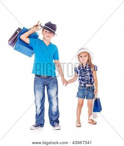 Fashionable children holding hands and shopping bags