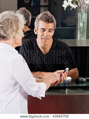 Hairdresser and female client discussing over mobilephone at salon counter