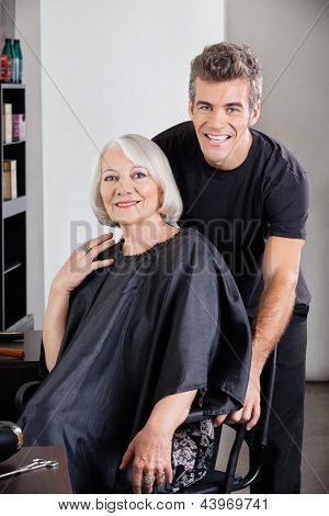 Portrait of happy female client and hairdresser at salon