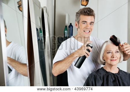 Portrait of hairdresser using hairspray to style female client's hair at beauty salon