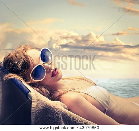 blonde woman in bikini sunbathing on the beach