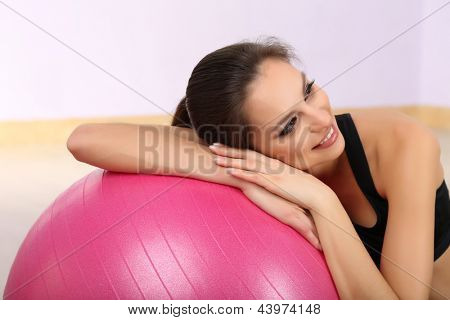 Young woman with gym ball at gymnasium