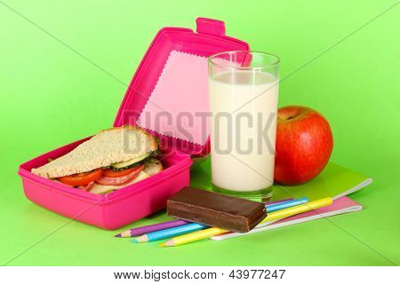 Lunch box with sandwich,apple,milk and stationery on green background