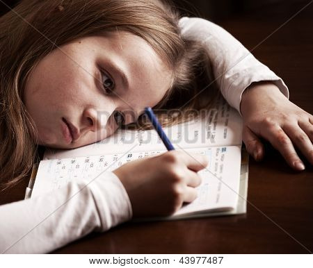 Child doing homework. Sad girl writing, reeding