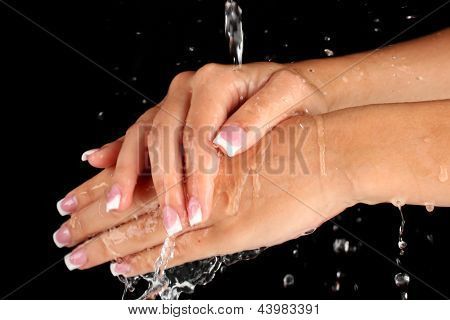 Washing woman's hands on black background close-up