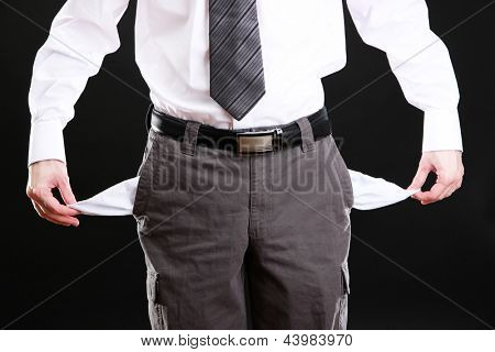 Business man showing his empty pockets, on black background