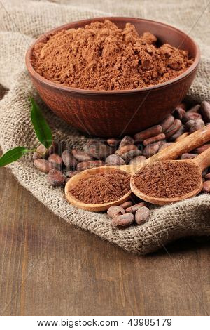 Cocoa powder and cocoa beans on wooden background